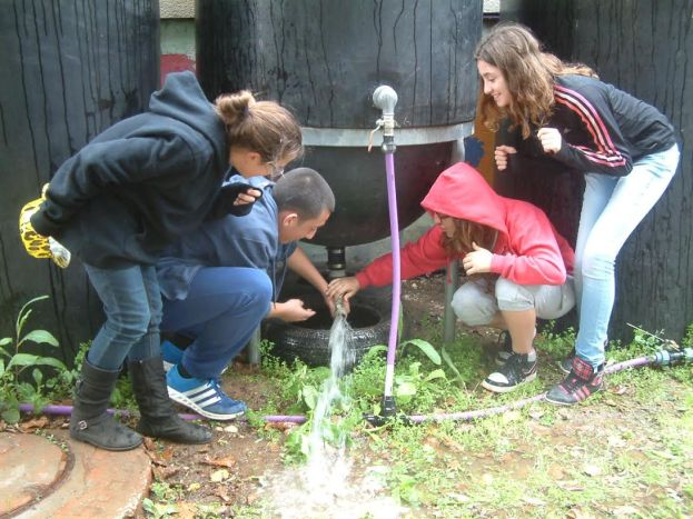 Students with rain barrel at Ganey Aviv