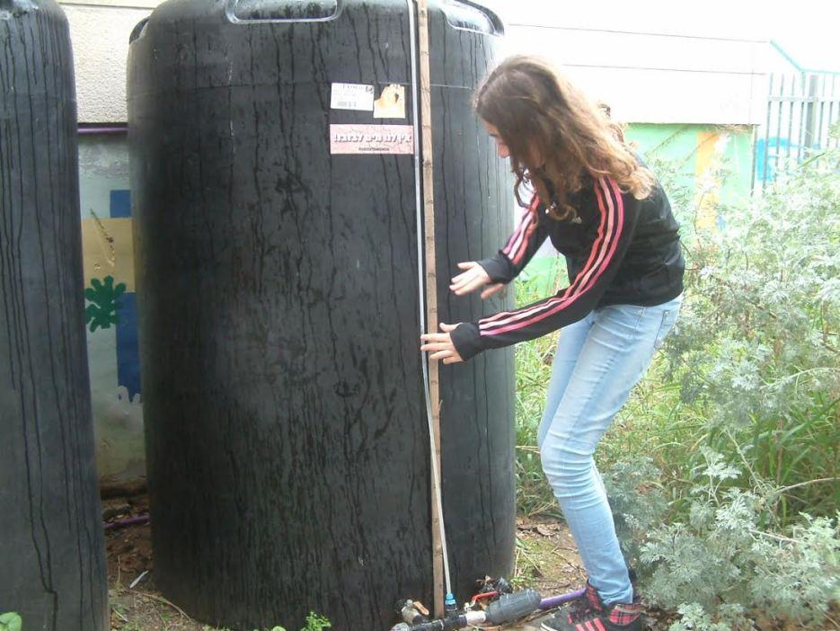 Student with rain barrel at Ganey Aviv